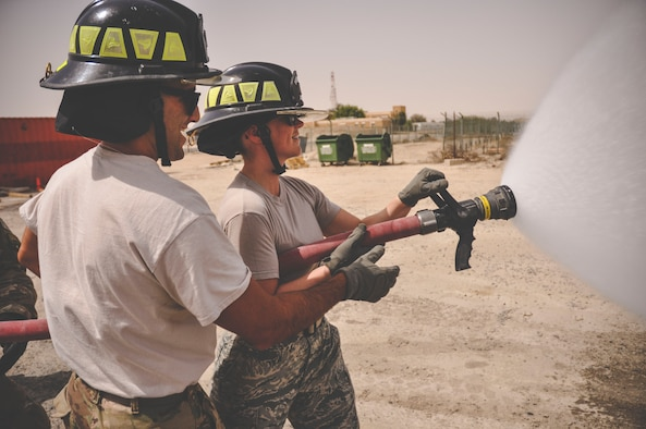 Senior Airman Kevin Angelesco, a firefighter assigned to the 386th Expeditionary Civil Engineer Squadron (left) supervises Staff Sgt. Jessica Moore, a mental health technician with the 386th Expeditionary Medical Group as she learns how to control a fire hose during a mental health unit familiarization visit at an undisclosed location in Southwest Asia, May 30, 2017. Angelesco is a reservist deployed from the 940th Civil Engineer Squadron, Beale Air Force Base, Calif.(U.S. Air Force Photo/Master Sgt. Eric M. Sharman)