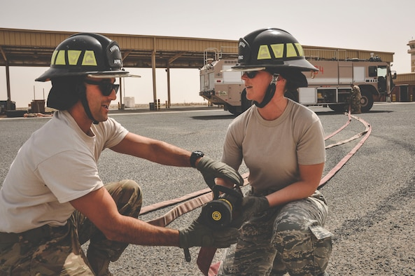 Senior Airman Kevin Angelesco a fire fighter assigned to the 386th Expeditionary Civil Engineer Squadron, (left) instructs Staff Sgt. Jessica Moore, a mental health technician with the 386th Medical Group on fire hose control during a mental health unit familiarization visit at an undisclosed location in southwest Asia, May 30, 2017. Moore regularly conducts unit visits to perform preventative mental health checks. (U.S. Air Force Photo/Master Sgt. Eric M. Sharman)