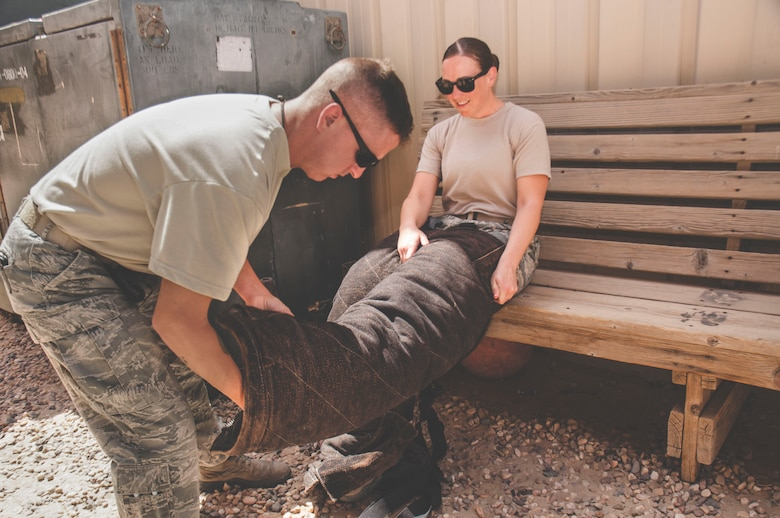 Tech. Sgt. Matthew Byrnes helps Staff Sgt. Jessica Moore into a bite suit during a mental health unit familiarization visit at an undisclosed location in southwest Asia, June 13, 2017. Moore frequently visits units that are likely to respond to trauma incidents. (U.S. Air Force Photo/Master Sgt. Eric M. Sharman)