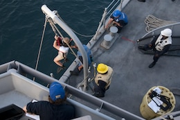 Ensign Maris Riley, a search-and-rescue swimmer assigned to USS Gladiator (MCM 11), is lowered into the water during a man-overboard drill conducted in the Arabian Gulf. Gladiator, one of four MCM ships forward deployed to Bahrain and attached to U.S. Naval Forces Central Command's Task Force 52, is a mine sweeper/hunter-killer capable of finding, classifying and destroying mines preserve the freedom of navigation and the free flow of commerce in the U.S. 5th Fleet area of operations.