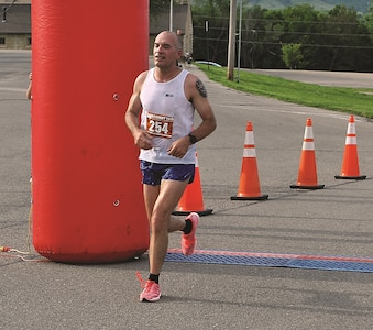 Sgt. 1st Class Darryl Jewell, Headquarters and Headquarters Company, 1st Armored Brigade Combat Team, 1st Infantry Division, crosses the finish line of the Ten-Miler Qualifier June 3 at King Field House.