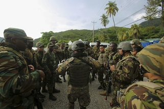 Service members from Belize, Jamaica, Trinidad and Tobago, and Mexican Marines discuss the objective before conducting a simulated raid on a hangar during Phase II of Exercise Tradewinds 2017 in Chaguaramas, Trinidad and Tobago, June 14, 2017. Tradewinds, sponsored by U.S. Southern Command, is an annual combined exercise designed to increase Caribbean security by enhancing the collective ability of the 20 participating nations to counter transnational organized crime and terrorism, and conduct humanitarian assistance and disaster relief operations. U.S. Marines are providing training and logistical support for Phase II of Tradewinds. (U.S. Marine Corps photo by Cpl. Luke Hoogendam)