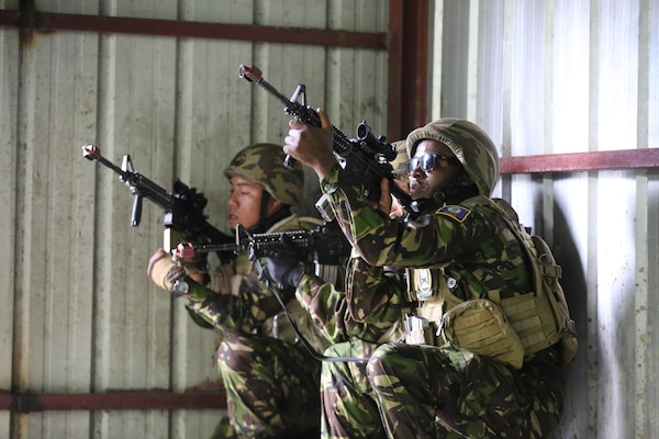 Members of the Belize Special Assignment Group provide security while conducting a simulated raid on an overtaken hangar during Phase II of Exercise Tradewinds 2017 in Chaguaramas, Trinidad and Tobago, June 14, 2017. Tradewinds, sponsored by U.S. Southern Command, is an annual combined exercise designed to increase Caribbean security by enhancing the collective ability of the 20 participating nations to counter transnational organized crime and terrorism, and conduct humanitarian assistance and disaster relief operations. U.S. Marines are providing training and logistical support for Phase II of Tradewinds. (U.S. Marine Corps photo by Cpl. Luke Hoogendam)