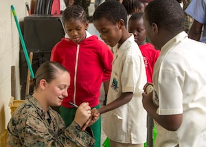 U.S. Marine Sgt. Olivia McDonald, a mass communicator with II Marine Expeditionary Force, signs a child's hand at Carenage Boy Government Primary School as part of a community relations event during Phase II of Exercise Tradewinds 2017 in Chaguaramas, Trinidad and Tobago, June 16, 2017. This year marks the 33rd iteration of the regionally focused, multi-nationally planned exercise, which dates back to 1984. McDonald, a Medford, Massachusetts, native, and other Marines are providing training and logistical support for the exercise. (U.S. Marine Corps photo by Sgt. Clemente C. Garcia)
