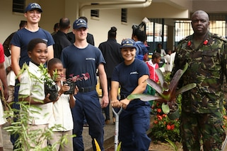 Trinidad and Tobago Defence Force Col. Roger Carter, right, the assistant chief staff officer of Headquarters, Trinidad and Tobago Defence Force, and U.S. Coast Guardsmen pose for a photo with students while at Carenage Boy Government Primary School as part of a community relations event during Phase II of Exercise Tradewinds 2017 in Chaguaramas, Trinidad and Tobago, June 16, 2017. Tradewinds, sponsored by U.S. Southern Command, brings together security forces and regional civilian agencies from 20 participating countries to strengthen relationships, build partner nation capacity and conduct subject matter expert exchanges in security-related operations. U.S. Marines are providing providing training and logistical support for Phase II of the exercise. (U.S. Marine Corps photo by Sgt. Olivia McDonald)
