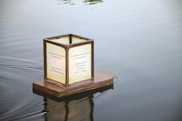 A lantern floats across Moon Lake after being placed in the water by Chap. (Capt.) Christopher Mohr May 29 during the lantern floating ceremony.