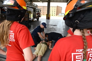 Fort Sam Houston firefighters Aaron Gaunt (left) and Randy Simeon (right) demonstrate chest compressions to students enrolled in the installation's Fire Explorer program at the JBSA-Fort Sam Houston Fire Station June 14. The two-week program allows students to experience some of what it takes to become a firefighter.