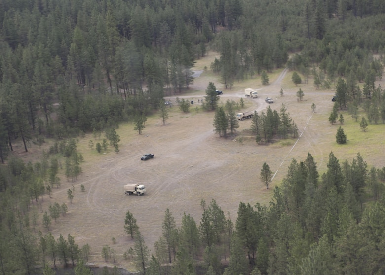 "A convoy from the Washington National Guard, C Company, 1st Battalion, 112th Airborne Regiment converge on a disabled truck with the assistance of a Lakota helicopter June 14, 2017, north of Fairchild Air Force Base, Washington. NG ground crews use Lakota helicopters to provide a ""eye in the sky"" for locating and directing Soldiers to target sites."
