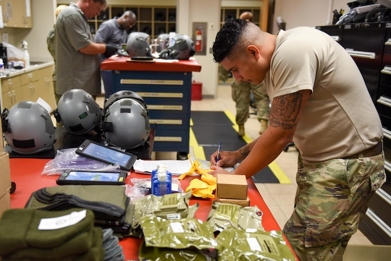 Tech. Sgt. Phillip Caicedo, an aircrew flight equipment technician with the 1st Special Operations Support squadron, packs an LRU-33A 20-man emergency life raft kit for an AC-130J Ghostrider at Hurlburt Field, Fla., June 15, 2017. Caicedo inspects the equipment required to complete the LRU-33A to ensure the equipment is not out of date and safe to use in the event of an in-flight emergency. (U.S. Air Force photo by Staff Sgt. Jeff Parkinson)