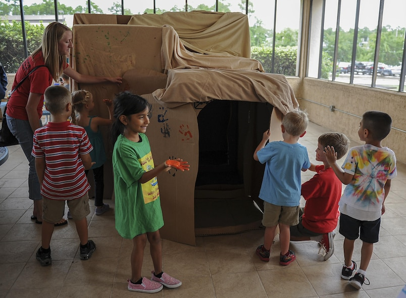 "Military children mark their handprints on a ""cave"" during the Summer Reading Program at the Landing Zone on Hurlburt Field, Fla., June 15, 2017. The young Air Commandos were sent ""back in time"" to be cavemen as part of the program's ""Reading by Design"" theme, exploring the history of architecture. (U.S. Air Force photo by Airman 1st Class Rachel Yates)"