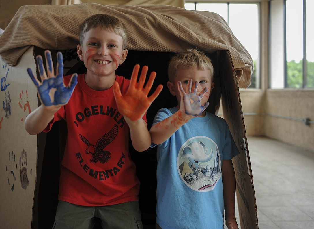 "Grant, 9, and Gunnar, 4, Cumming show off their painted hands during the Summer Reading Program at the Landing Zone at Hurlburt Field, Fla., June 15, 2017. Grant and Gunnar, along with the other several dozen young Air Commandos, embarked on an imaginary dinosaur hunt and marking a ""cave"" with their handprints after their success. (U.S. Air Force photo by Airman 1st Class Rachel Yates)"