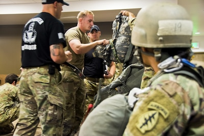Army Sgt. Daniel Durkee, center, a mechanic assigned to the 10th Special Forces Group, performs a jumpmaster personnel inspection, May 19, 2017, as his wife, Sgt. Angel Durkee, foreground, watches during a static-line jumpmaster course at Fort Carson, Colo. Army photo by Staff Sgt. William Reinier