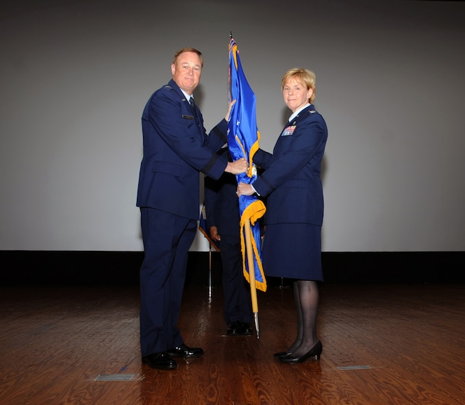 Maj. Gen. Darryl Burke (left), Air Force District of Washington commander, receives the 79th Medical Wing guidon from Col. Sharon Bannister, former 79th Medical Wing commander, during an in-activation ceremony June 16, 2017 at Joint Base Andrews, Md. Bannister had led the wing since assuming command 2015 and its approximately 1,500 Air Force health care professionals operating in eight locations and providing Air Force medical forces for expeditionary deployment, homeland defense operations and operations worldwide. (Photo by Staff Sgt. Joe Yanik)