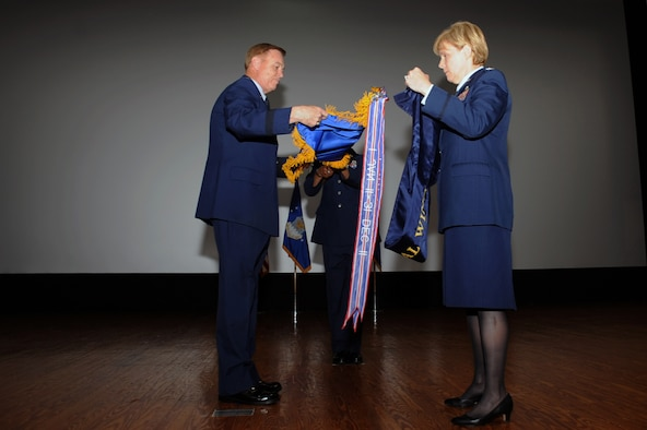 Maj. Gen. Darryl Burke (left), Air Force District of Washington commander, and Col. Sharon Bannister, former 79th Medical Wing commander, furl and case the wing's guidon during an in-activation ceremony June 16, 2017 at Joint Base Andrews, Md. The guidon will be stored in the National Museum of the U.S. Air Force, Dayton, Ohio, in the event the wing is re-activated. (Photo by Staff Sgt. Joe Yanik)
