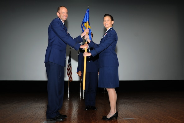 Col. E. John Teichert (left), 11th Wing commander, passes the 11th Medical Group guidon to Col. Leslie Knight, 11the MDG commander, during an inactivation ceremony June 16, 2017 at Joint Base Andrews, Md. The ceremony, presided over by Maj. Gen. Darryl Burke, Air Force District of Washington commander, marked the in-activation of the 79th Medical Wing and the activation of the 11th Medical Group.(Photo by Staff Sgt. Joe Yanik)