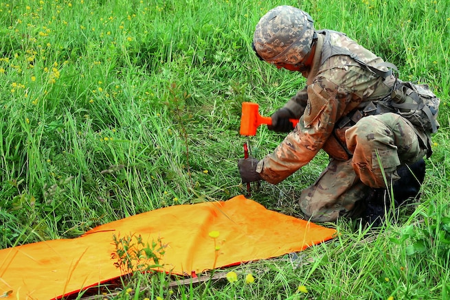 New York Army National Guard Pfc. Nicholas Timbrouck places a panel to mark the landing zone for a UH-60 Black Hawk helicopter during an air assault artillery raid at Fort Drum, N.Y., June 9, 2017. Timbrouck is a cannon crewmember assigned to Alpha Battery, 1st Battalion, 258th Artillery Regiment, 27th Infantry Brigade Combat Team. Army National Guard photo by Sgt. Alexander Rector