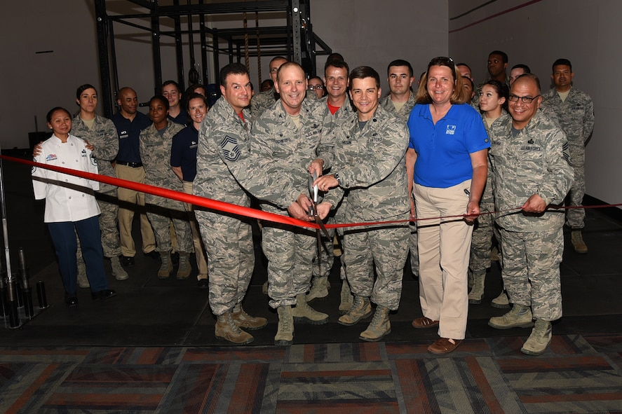 Col. Doug Schiess, 21st Space Wing commander, along with Airmen from the 21st Civil Engineer Squadron and 21st Force Support Squadron, cuts the ribbon for the grand opening of 24 Hour Fitness at the Fitness Center, Peterson Air Force Base, Colo., June 16, 2017. Military ID registration for 24 Hour Fitness 24/7 access is now available at the Fitness Center. (U. S. Air Force photo by Robb Lingley)