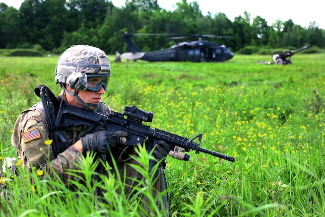 Army Pfc. Michael Natole provides security stands during an air assault artillery raid at Fort Drum, N.Y., June 9, 2017. Natole is a cannon crewmember assigned to Alpha Battery, 1st Battalion, 258th Artillery Regiment, 27th Infantry Brigade Combat Team of the New York Army National Guard. Army National Guard photo by Sgt. Alexander Rector