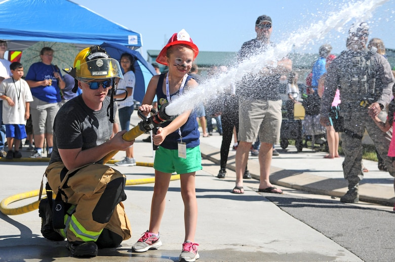 Senior Airman Brody Sanzone, a firefighter with the 151st Civil Engineering Squadron, helps a young girl direct a fire hose toward an orange traffic cone to simulate extinguishing a fire during Wingman Day on June 10, 2017 at Roland R. Wright Air National Guard Base in Salt Lake City. (U.S. Air National Guard photo by Tech. Sgt. Amber Monio)
