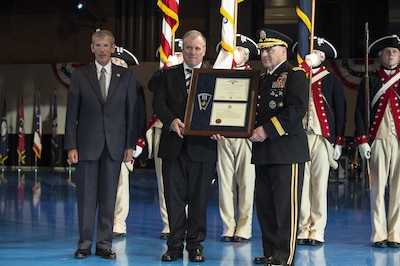 As part of a twilight tattoo event at Joint Base Myer-Henderson Hall, Va., held on honor of the Army's 242nd birthday, Acting Secretary of the Army Robert Speer, left, and Chief of Staff of the Army Gen. Mark A. Milley, right, present a posthumous Distinguished Flying Cross for Army Capt. James E. Miller to Miller's great-grandson, Byron Derringer, center, June 14, 2017. Army photo by Spc. Trevor Wiegel