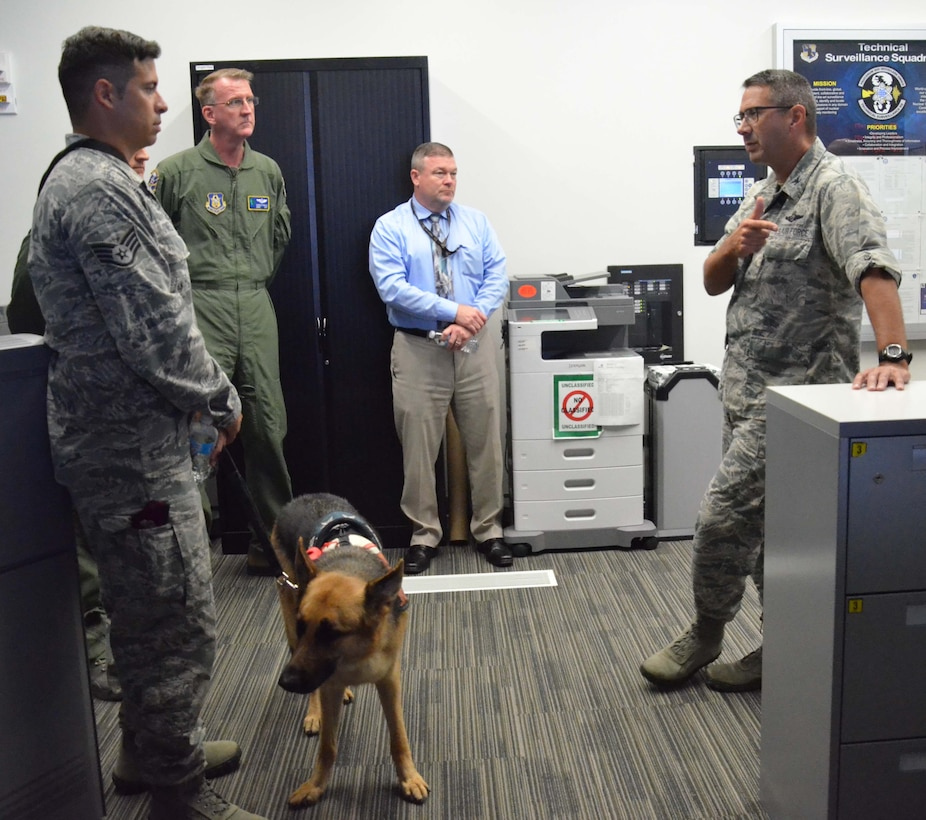 Col. Jon VanNoord (right), director of operations for the Air Force Technical Applications Center, Patrick AFB, Fla., briefs Staff. Sgt. August O'Niell (left), the Air Force's first pararescue amputee, during O'Niell's visit to the nuclear treaty monitoring center May 22, 2017.  Pictured with O'Niell is his service dog and constant companion, Kai.  (U.S. Air Force photo by Susan A. Romano)