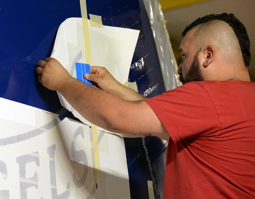Richard Barber, 576th Aircraft Maintenance Squadron painter, applies a masking stencil to the vertical stabilizer of Fat Albert on May 23 at Hill Air Force Base, Utah. The stencil is part of the main Blue Angels logo painted on the aircraft. (U.S. Air Force Photo by Alex R. Lloyd)