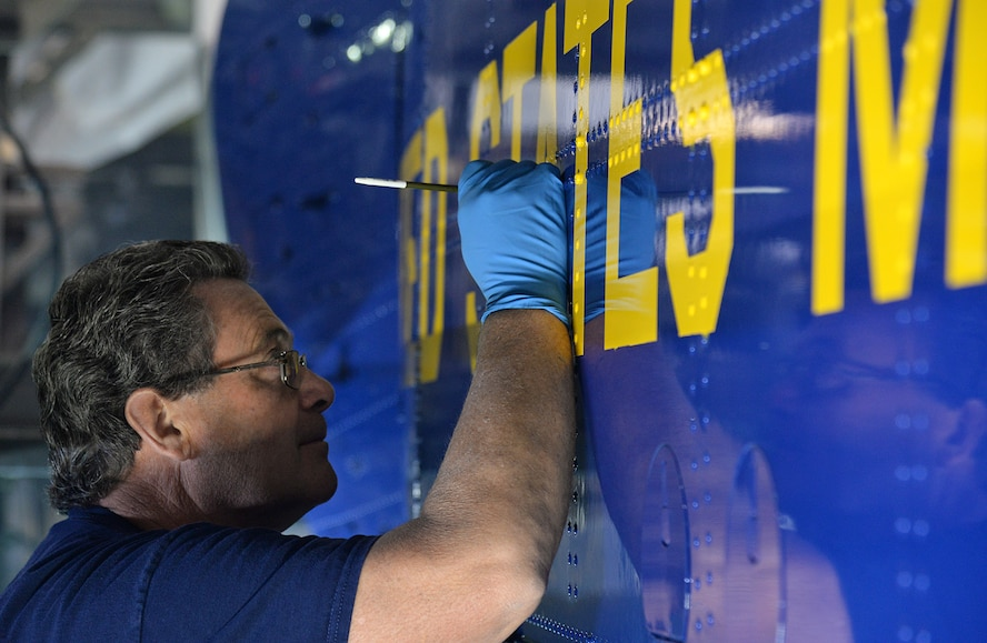 576th Aircraft Maintenance Squadron Painter Terrel Fry uses a steady hand to apply touchup paint to the side of Fat Albert on May 31 at Hill Air Force Base, Utah. Paying close attention to detail helps showcase the pride in workmanship for the paint crew.  (U.S. Air Force Photo by Alex R. Lloyd)