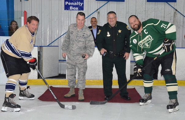 Col. Steven M. Gorski, commander of the Air Force Technical Applications Center, Patrick AFB, Fla., and Brevard County Sheriff Wayne Ivey, drop ceremonial pucks as Bill Hungate, AFTAC's captain, and Brad Cervi, BCSO's captain, prepare for the faceoff.  The two teams met in a charity match June 10, 2017 to raise money for the Space Coast Sled Hockey program.  (U.S. Air Force photo by Susan A. Romano)