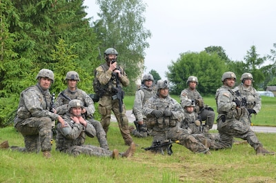 A combined forces squad featuring members of the Minnesota Army National Guard's 1st Armored Brigade Combat Team, 34th Infantry Division, British Royal Marines and Polish soldiers wait at a collection point for the medical evacuation of simulated casualties during Exercise Saber Strike 17 near Sventezeris, Lithuania, June 18, 2017. Army photo by Sgt. Shiloh Capers