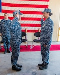 DLA Distribution Sigonella, Italy, comannder Navy Supply Corps Capt. Pamela Dozier is administered the oath of office by Capt. Christopher Parker, Fleet Logistics Center Sigonella commander, during her May 31 promotion ceremony.