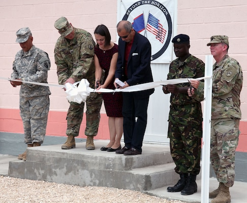Completion of the new building at the Ladyville Health Clinic is officially marked at the ribbon-cutting ceremony June 9 in Ladyville, Belize. Shown cutting the ribbon (from left): Chief Warrant Officer 3 Herminio Romero, site project manager and member of the 448th Engineer Battalion from Puerto Rico; Col. John Simma, Beyond the Horizon 2017 Task Force Jaguar commander; Adrienne Galanek, Chargé d'Affaires for the U.S. Embassy Belize; Ramon Figueroa, CEO of the Belize Ministry of Health; Lance Cpl. Gladden of the Belize Defence Force and Lt. Col. Robert Ramsey, Senior Defense Official and Defense Attaché for the U.S. Embassy. Construction was accomplished during Beyond the Horizon 2017, a collaborative training event between U.S. Army South, the Belize Defence Force, other Central American nations and local and international NGOs, providing medical and engineering services throughout Belize.
