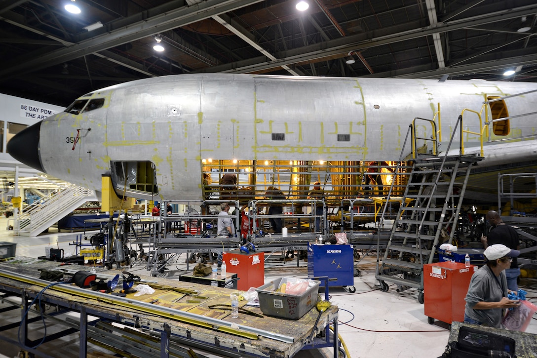 Sheet metal mechanics with the 76th Aircraft Maintenance Group working on the KC-135 Programmed Depot Maintenance line perform a double belly skin removal. Although a single belly removal is normally called for in PDM, double belly removals are not unusual and are required when both sides of the aircraft have corrosion and other defects. (Air Force photo by Kelly White)
