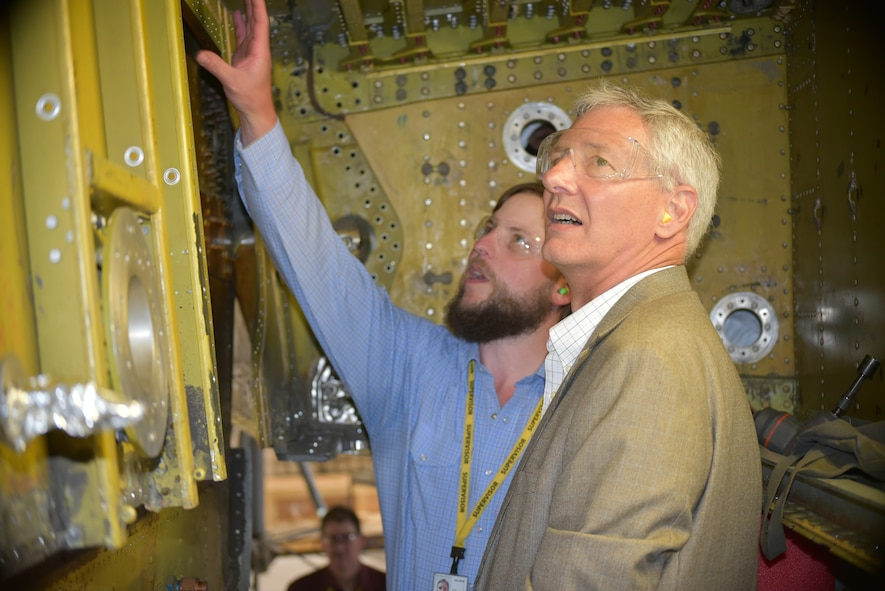 "Daron Bender, a sheet metal chief with the 564th Aircraft Maintenance Squadron, left, provides Wayne Schatz Jr., associate deputy chief of staff for operations, headquarters, United States Air Force, with an overview of the aft wing terminal fitting and center wing spar replacement procedures being performed on the KC-135 ""Stratotanker"" during his visit to Tinker Air Force Base May 22-23. During his two-day visit, Schatz was able to discuss and receive updates on Air Force Sustainment Center logistics and sustainment, to include updates on the E-3 ""Sentry"" Airborne Warning and Control System aircraft, as well as impacts to fleet health and readiness as pilot production increases on Air Force weapon systems. (Air Force photo by Darren D. Heusel)"