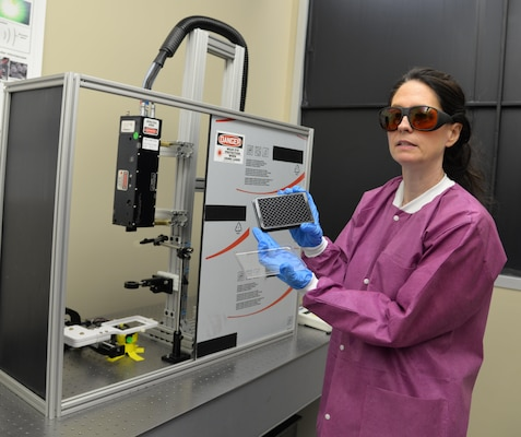 Dr. Nancy Millenbaugh, research chemist and principal investigator for the Craniofacial Health and Restorative Medicine Directorate at Naval Medical Research Unit San Antonio, holds a plate which is used for testing samples of biofilms for research into the effectiveness of nanoparticle targeted laser therapy in improving the treatment of multi-drug resistant wound infections, especially for servicemembers with maxillofacial injuries from combat. Researchers are hoping to develop a nanoparticle laser therapy that can breakdown biofilms, which contain a protecting coating produced by bacteria that make infections in the wound resistant to antibiotic treatment.