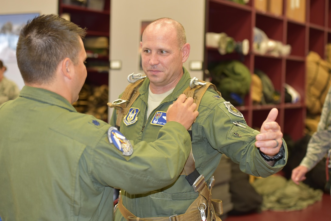 Lt. Col. Ryan Montanez, (left) combat rescue officer and 308th Rescue Squadron commander, outfits 920th Rescue Wing, Commander Kurt A. Matthews, Patrick Air Force Base, Florida, with skydiving gear. The commander, along with the 45th Space Wing commander, Brig. Gen. Wayne R. Monteith, co-located at PAFB, skydived to demonstrate their commitment to mutual-support and shared resources in an unforgettable way June 8, 2017. (U.S. Air Force photo / Senior Airman Brandon Kalloo Sanes)