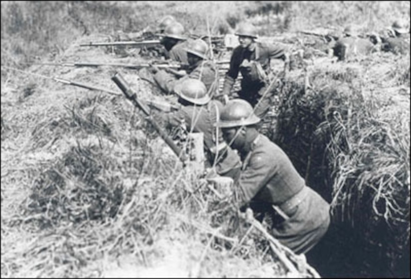 African-American Soldiers (and one of their white officers) of the 369th Infantry practice what they will soon experience, fighting in the trenches of the Western Front. They are wearing French helmets and using French issued rifles and equipment, the logic being that since they were fighting under French command, it was easier to resupply them from the French system than trying to get American-issued items. (Photo by National Archives and Records Administration)