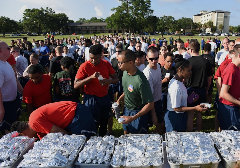 Keesler personnel help themselves to breakfast burritos before beginning field day activities June 15, 2017, on Keesler Air Force Base, Miss. Field day was the final event of Wingman Week, which focused on the physical pillar of Comprehensive Airman Fitness, resiliency and teambuilding initiatives across the base. (U.S. Air Force photo by Kemberly Groue)