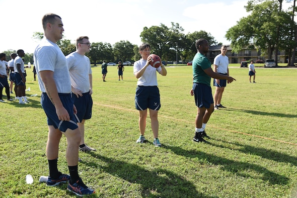 Col. Debra Lovette, 81st Training Wing commander, throws a football with Airmen from the 81st Medical Operations Squadron during field day events June 15, 2017, on Keesler Air Force Base, Miss. Field day was the final event of Wingman Week, which focused on the physical pillar of Comprehensive Airman Fitness, resiliency and teambuilding initiatives across the base. (U.S. Air Force photo by Kemberly Groue)