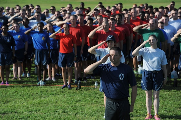 Tech. Sgt. Roger Anderson III, 81st Training Group military training leader, and Keesler personnel renders salutes during the singing of the National Anthem during field day June 15, 2017, on Keesler Air Force Base, Miss. Field day was the final event of Wingman Week, which focused on the physical pillar of Comprehensive Airman Fitness, resiliency and teambuilding initiatives across the base. (U.S. Air Force photo by Kemberly Groue)