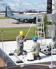 U.S. Air Force Airmen from the 210th Engineering Installation Squadron add an antenna to a newly installed Giant Voice stack located on the roof of the Small Air Terminal at the 133rd Airlift Wing in St. Paul, Minn., June 19, 2017. Once complete, the system will provide improved emergency notification capabilities to flight line and maintenance personnel while aircraft engines are running. Strobes will also light up on top of the stack as an added visual durning alerts.   