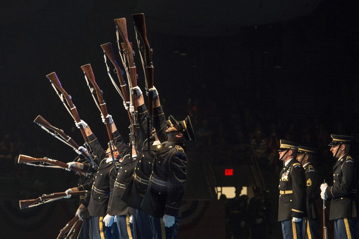 Army drill team members perform at night.