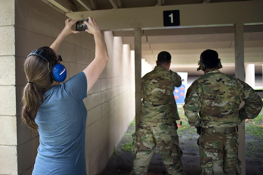 Christie Patterson, the wife of a Special Operations Command Central (SOCCENT) service member, takes a photo of her husband firing a handgun during Spartan Spouse Day at MacDill Air Force Base, June 13, 2017. During the day, spouses of SOCCENT members learned how to properly load, fire and unload a handgun. (U.S. Air Force photo by Airman 1st Class Caleb Nunez)