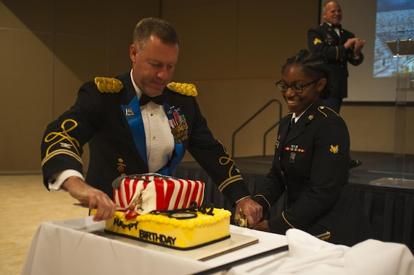 U.S. Army Col. Brian Lieb, and Spc Alantra Grigsby, 344th Military Intelligence Battalion, cut the party cake during the Army Ball at the McNease Convention Center San Angelo, Texas, June 16, 2017. Lieb and Alantra are the oldest and youngest (respectively) soldiers present at the ball, and tradition has them together cutting the cake. (U.S. Air Force photo by Senior Airman Scott Jackson/Released)