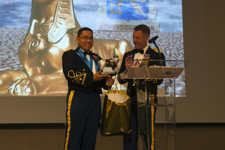 U.S. Army Lt. Col. Yukio Kuniyuki, 344th Military Intelligence Battalion Commander, gifts a Lt. Col. Ewe Little figurine to Col. Brian Lieb, during the Army Ball at the McNease Convention Center San Angelo, Texas, June 16, 2017. Ewe Little is a sheep statue posted outside Goodfellow Air Force Base, a gift from the local city San Angelo. San Angelo at one point had a massive sheep population and the sheep has since become the city's mascot. Every organization gifted a sheep by the city has their own design. (U.S. Air Force photo by Senior Airman Scott Jackson/Released)