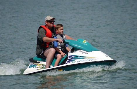 Ensuring they have proper-fitting lifejackets on, a father and son enjoy a ride on Black Butte Lake.