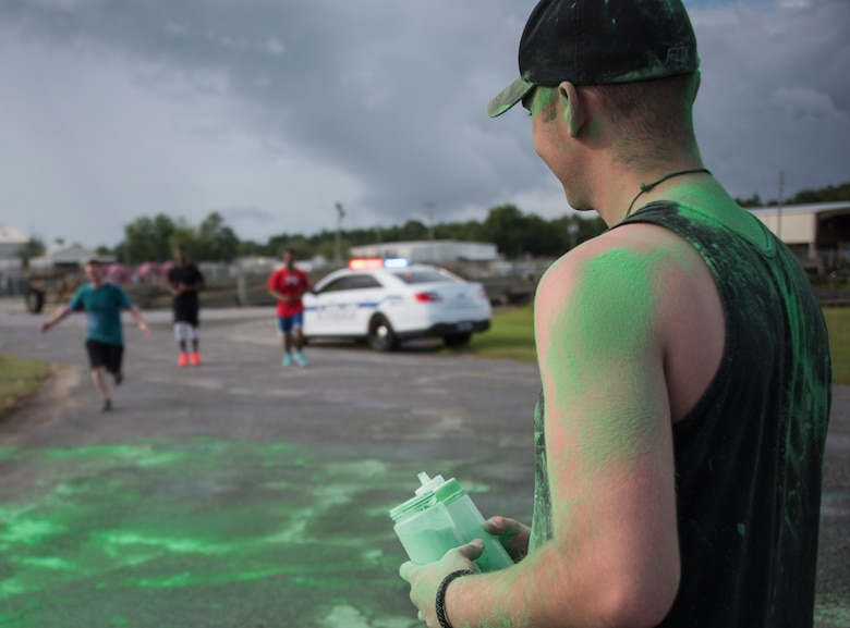 A volunteer stands ready with his containers of colored chalk as runners approach the finish line during the LGBT Pride Month 5K Color Run June 14 at Eglin Air Force Base, Fla. The run was held to celebrate diversity and to raise inclusion awareness. (U.S. Air Force photo/Ilka Cole)