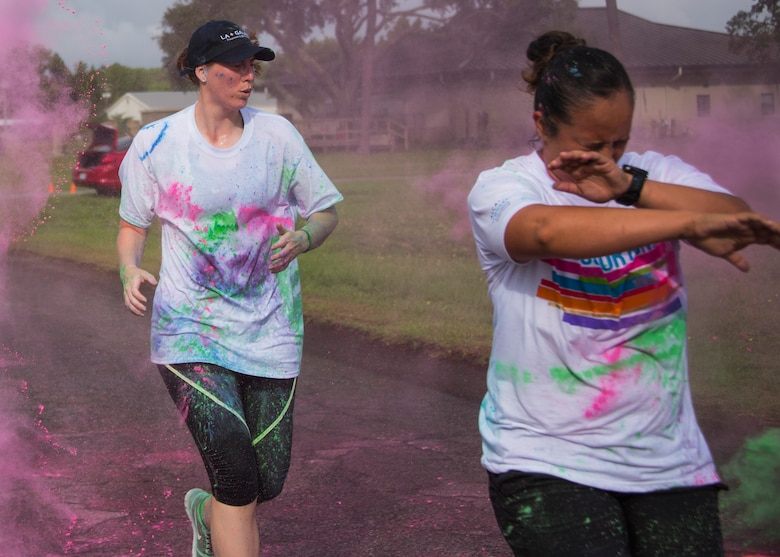 Runners sprinkled with color run through a cloud of colored chalk as they approach the finish line of the LGBT Pride Month 5K Color Run June 14 at Eglin Air Force Base, Fla. The run was held to celebrate diversity and raise inclusion awareness. (U.S. Air Force photo/Ilka Cole)