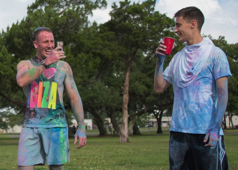 A runner covered in color captures a photo of his friend sipping water at the end of the LGBT Pride Month 5K Color Run June 14 at Eglin Air Force Base, Fla. The run was held to celebrate diversity and raise inclusion awareness. (U.S. Air Force photo/Ilka Cole)