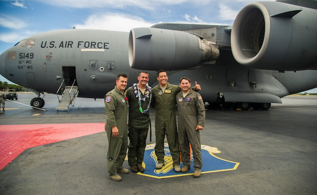 Maj. Justin Carmona, 535th Operations Support Squadron pilot, Col. Charles Velino, 15th Operations Group commander, Capt. Reinier Villanueva, 15th Operations Support Squadron C-17 flight instructor pilot, and Tech. Sgt. Todd Barney, 15th Operations Support Squadron loadmaster, pose for a photo after Velino's final flight at Joint Base Pearl Harbor-Hickam, Hawaii, June 16, 2017.  Velino is a command pilot with over 3,500 flying hours and will be leaving the 15th Operations Group to take command of the 47th Flying Training Wing in Laughlin AFB, Texas. (U.S. Air Force photo by Tech Sgt. Heather Redman)