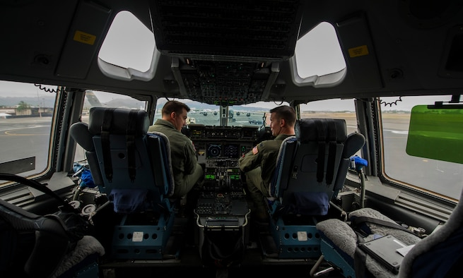Col. Charles Velino, 15th Operations Group commander, and  Maj. Justin Carmona, 535th Operations Support Squadron pilot, conduct pre-flight checks onboard a C-17 Globemaster III for Velino's final flight at Joint Base Pearl Harbor-Hickam, Hawaii, June 16, 2017.  Velino is a command pilot with over 3,500 flying hours and will be leaving the 15th Operations Group to take command of the 47th Flying Training Wing in Laughlin AFB, Texas. (U.S. Air Force photo by Tech Sgt. Heather Redman)
